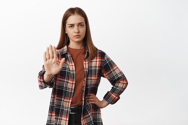 Młoda kobieta wygląda na zmęczoną i podnosi rękę w bloku, mówi nie, odmawia zabrania lub odrzuca coś rozczarowuje, każe trzymać się z daleka, stoi pod białą ścianą.