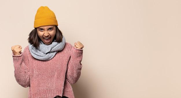 Młoda kobieta wyglądająca na nieprzyjemnie zszokowaną, przestraszoną lub zaniepokojoną, z szeroko otwartymi ustami i zakrywającymi uszy dłońmi