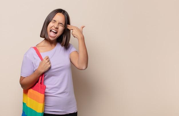 Młoda kobieta wyglądająca na nieszczęśliwą i zestresowaną, samobójczy gest wykonujący znak pistoletu ręką, wskazujący na głowę
