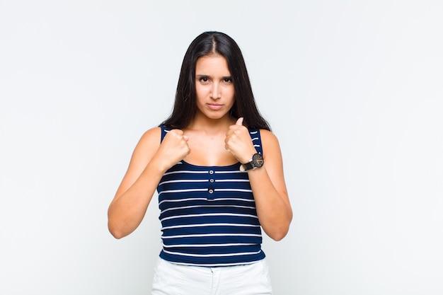 Młoda kobieta wyglądająca na pewną siebie, wściekłą, silną i agresywną, z pięściami gotowymi do walki w pozycji bokserskiej