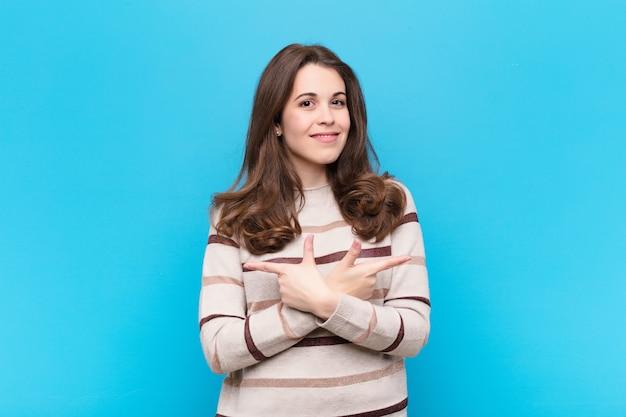 Młoda kobieta wyglądająca na zaskoczoną i zdezorientowaną, niepewna i wskazująca w przeciwnych kierunkach z wątpliwościami na niebieskiej ścianie