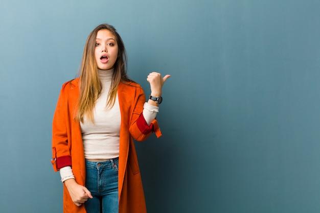 Młoda kobieta wyglądająca na zaskoczoną z niedowierzaniem, wskazująca na przedmiot z boku i mówiąca wow, niewiarygodne