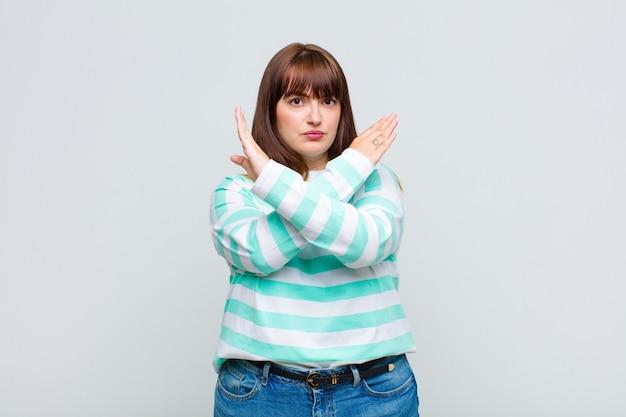 Młoda kobieta wyglądająca na zirytowaną i znudzoną twoim nastawieniem, mówi dość! ręce skrzyżowane z przodu, nakazujące przestać