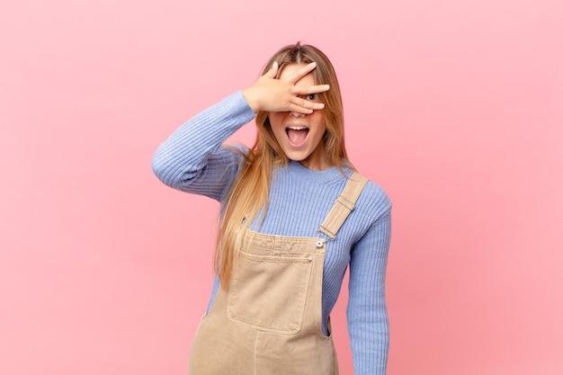 Młoda kobieta wyglądająca na zszokowaną, przestraszoną lub przerażoną, zakrywa twarz dłonią