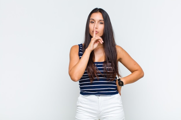 Młoda kobieta wyglądająca poważnie i krzywo, z palcem przyciśniętym do ust, domagająca się ciszy lub spokoju, zachowująca tajemnicę
