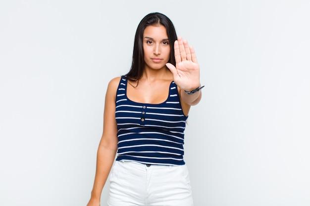 Młoda kobieta wyglądająca poważnie, surowo, niezadowolona i wściekła pokazuje otwartą dłoń wykonującą gest stopu
