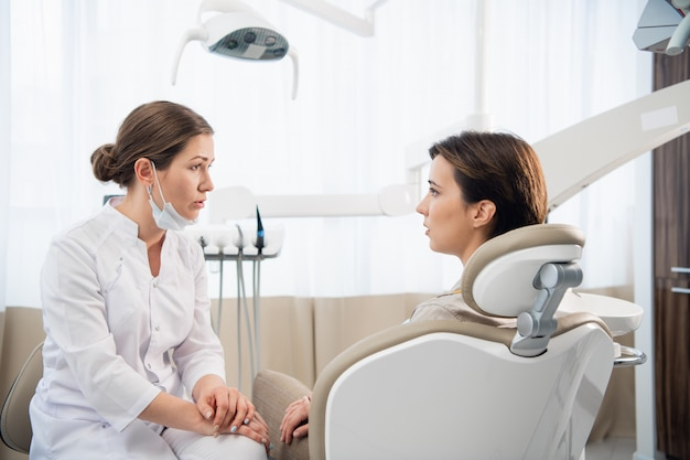 Młoda kobieta wyjaśnia swoje problemy dentystyczne lekarzowi, który słucha uważnie