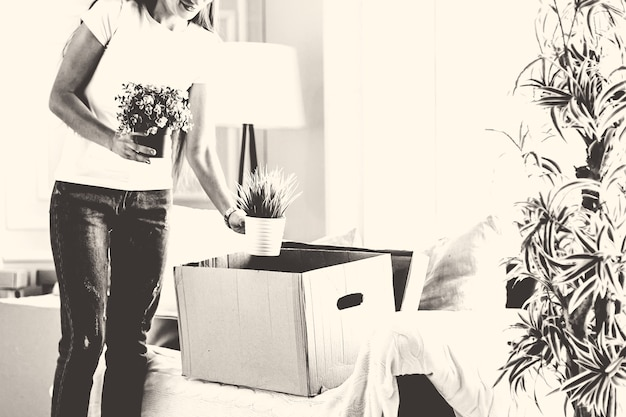 Młoda kobieta wyjmuje swoje ulubione rośliny z kartonu. przeprowadzka do nowego mieszkania