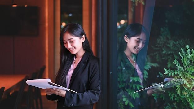 Młoda kobieta wykonawczy czytając dokument w dłoniach podczas pracy w biurze.