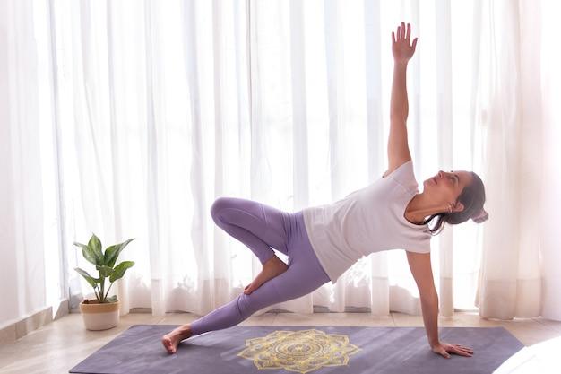 Młoda kobieta wykonuje asanę jogi na jednej nodze deski bocznej (eka pada vasisthasana)