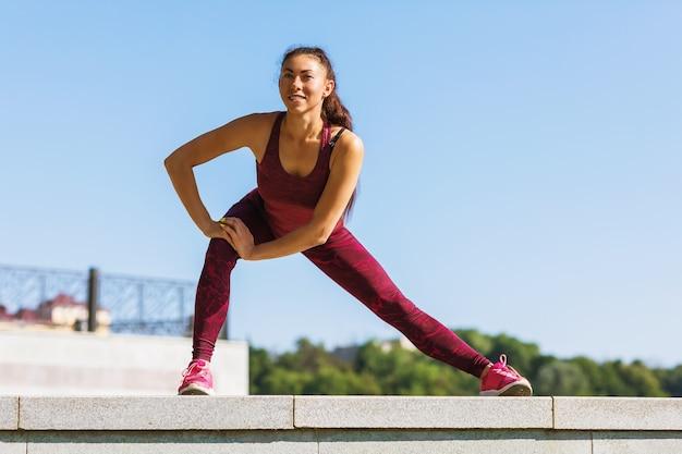 Młoda kobieta wykonuje ćwiczenia rozciągające w słoneczny letni poranek na świeżym powietrzu