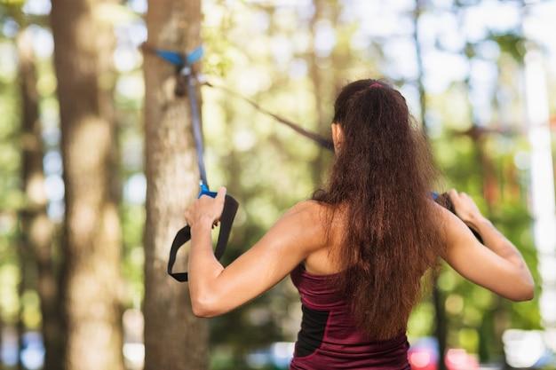 Młoda kobieta wykonuje ćwiczenie mięśni pleców za pomocą pasów fitness przymocowanych do drzewa w parku