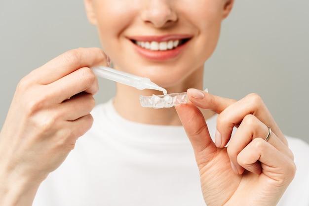 Młoda kobieta wykonuje zabieg wybielania zębów w domu na tacce wybielającej z żelem
