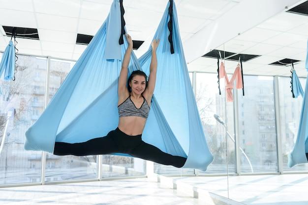 Młoda Kobieta Wykonywanie ćwiczeń Latającej Jogi Premium Zdjęcia