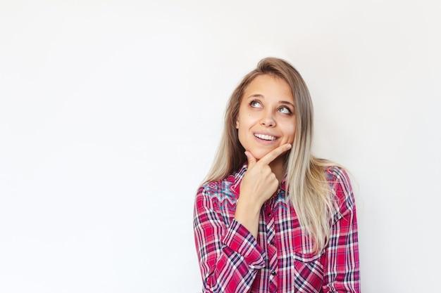 Młoda kobieta wyobraża sobie lub myśli, patrząc na puste miejsce na reklamy, oferta promocyjna, cytat tekst