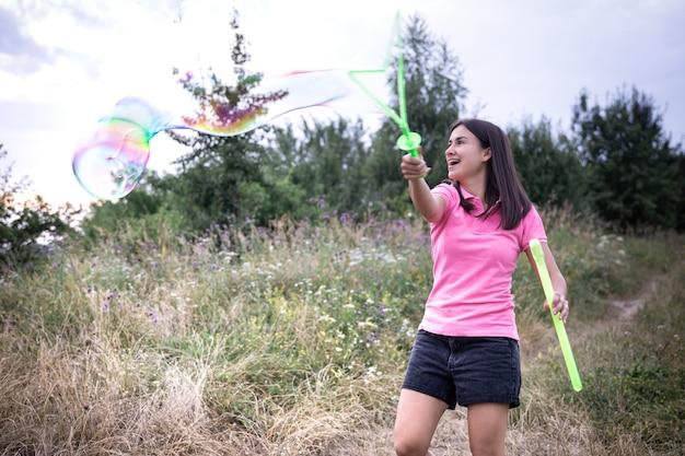 Młoda kobieta wypuszcza duże kolorowe bańki mydlane wśród trawy na łonie natury.