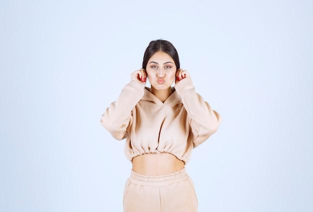 Młoda kobieta wyrywająca uszy na znak przesądu