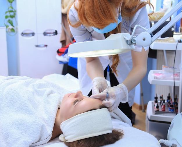 Młoda kobieta wyrywanie brwi pęsetą z bliska.