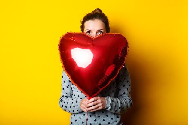 Młoda kobieta wystającym zza czerwonego balonu w formie serca na żółtym tle.