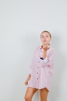 Młoda kobieta wysyła pocałunek w różowej koszuli i wygląda atrakcyjnie