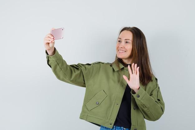 Młoda kobieta wysyła pozdrowienia do kogoś na telefon w zielonej kurtce i szuka zadowolony, widok z przodu.
