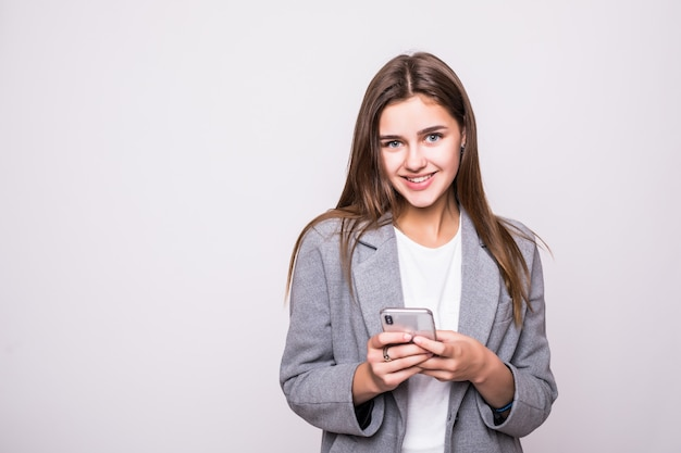 Młoda kobieta wysyła sms na telefonie komórkowym, odizolowywającym na białym tle
