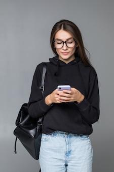 Młoda kobieta wysyła sms na telefonie komórkowym, odizolowywającym na biel ścianie