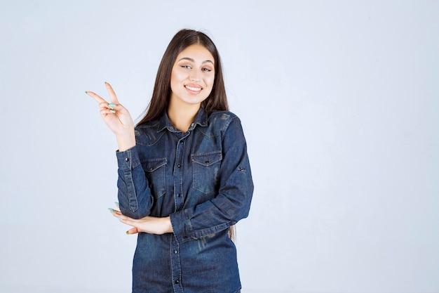 Młoda kobieta wysyła światu pokój i przyjaźń