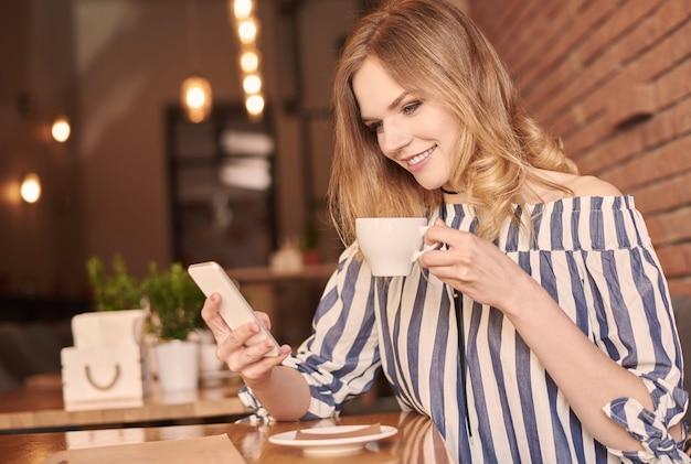 Młoda kobieta wysyła wiadomości tekstowe podczas picia kawy