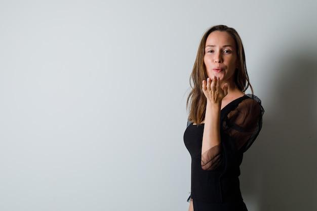 Młoda kobieta wysyłająca buziaki z przodu w czarnej bluzce i czarnych spodniach i wyglądająca czarująco