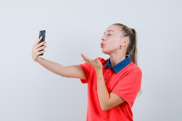 Młoda kobieta wysyłająca pocałunek podczas robienia selfie w koszulce