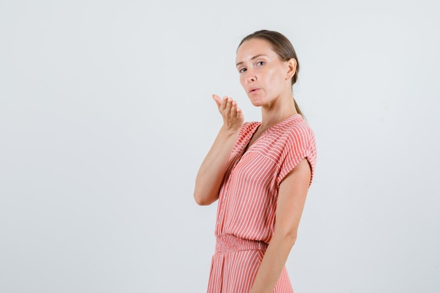 Młoda kobieta wysyłająca pocałunek powietrza w pasiastej sukience.