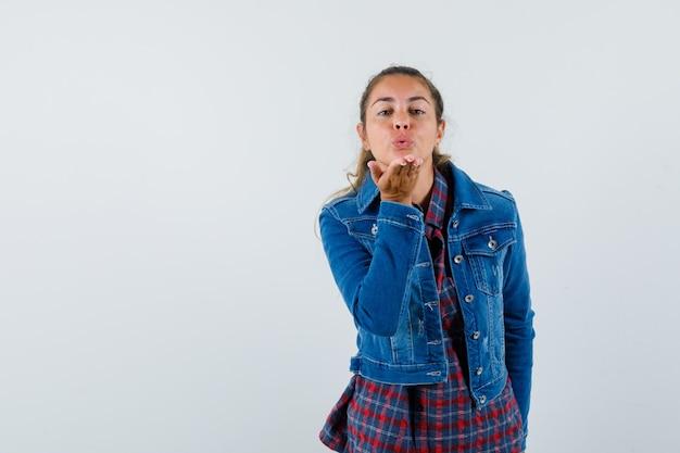 Młoda kobieta wysyłająca pocałunek w koszulę, kurtkę i kuszący wygląd, widok z przodu.