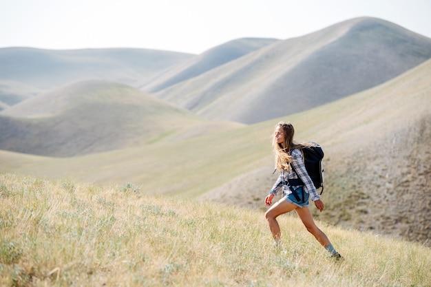 Młoda kobieta wznosząca się na duchu wspina się po zboczu, w otoczeniu pięknej scenerii wzgórza. wybrała szybkie tempo, stawiając szerokie, sprężyste kroki.