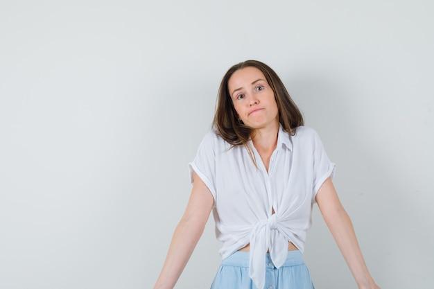 Młoda kobieta wzrusza ramionami w białej bluzce i jasnoniebieskiej spódnicy i wygląda zamyślona