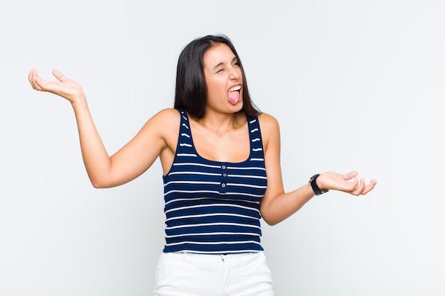 Młoda kobieta wzruszająca ramionami z głupim, szalonym, zdezorientowanym wyrazem twarzy, zirytowana i nieświadoma