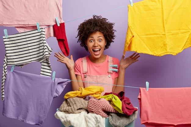 Młoda kobieta z afro stwarzające z praniem w kombinezonie