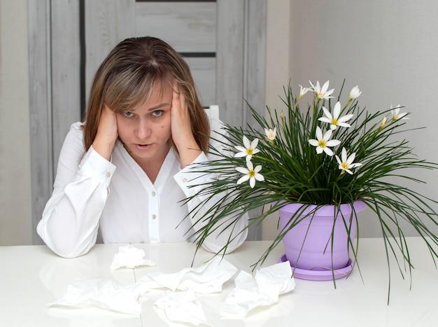 Młoda kobieta z alergią, trzymająca się za głowę. kwiaty na pierwszym planie. dziewczyna cierpiąca na alergie.