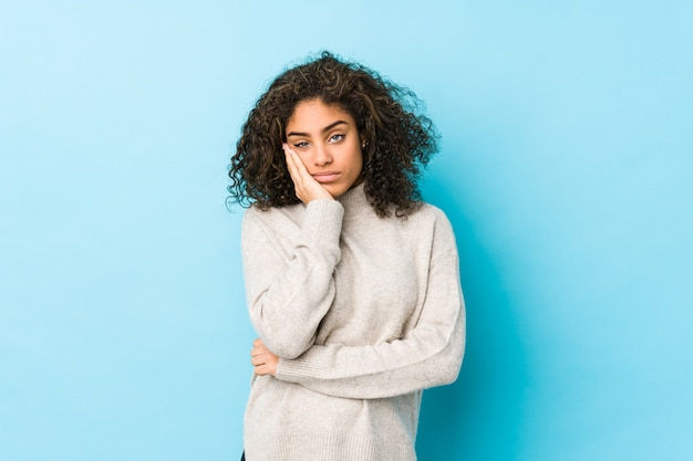 Młoda kobieta z amerykańskimi kręconymi włosami, która jest znudzona, zmęczona i potrzebuje dnia relaksu.