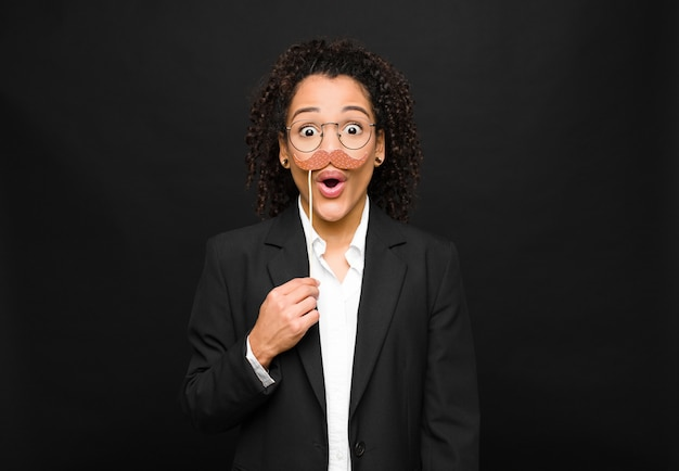 Młoda kobieta z ameryki łacińskiej, wyglądająca na bardzo zszokowaną lub zaskoczoną, wpatrująca się z otwartymi ustami, mówiąc: wow żartuje z wąsem