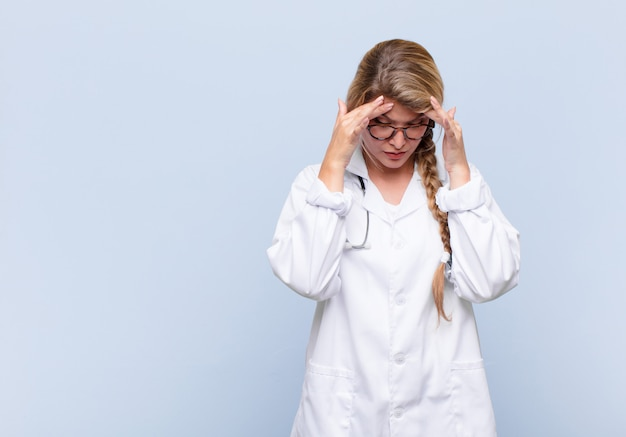 Młoda kobieta z ameryki łacińskiej, zestresowana i sfrustrowana, pracująca pod presją z bólem głowy i niepokojąca się problemami. koncepcja lekarza