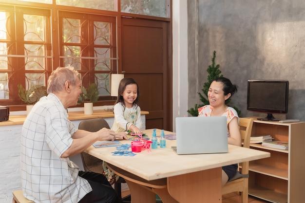 Młoda kobieta z azjatyckiego biznesu korzysta z laptopa w domu, podczas gdy córka bawi się i odrabia pracę domową, ucząc dziadka