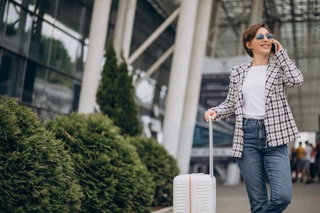 Młoda kobieta z bagażem na lotnisku podróżuje i rozmawia przez telefon