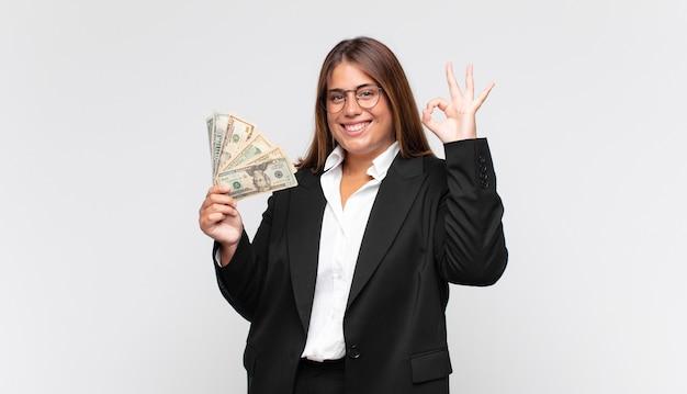 Młoda kobieta z banknotami czuje się szczęśliwa, zrelaksowana i usatysfakcjonowana, pokazując aprobatę z dobrym gestem, uśmiechając się