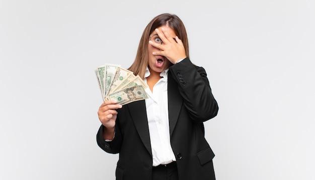 Młoda kobieta z banknotami wyglądająca na zszokowaną, przestraszoną lub przerażoną, zakrywająca twarz dłonią i zerkająca między palcami