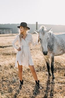 Młoda kobieta z białym koniem stojącym na farmie.