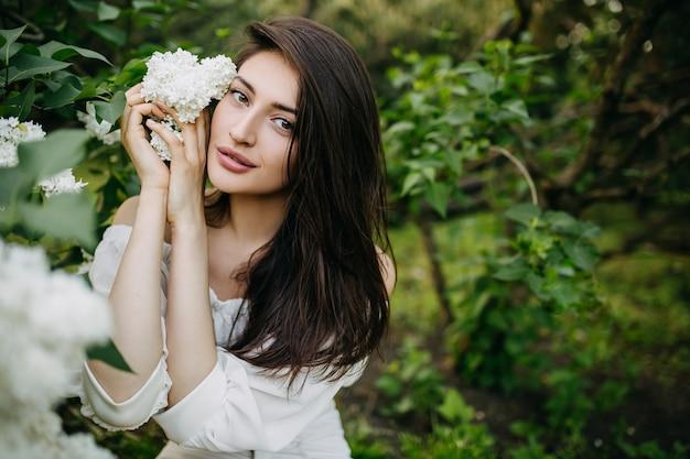 Młoda kobieta z białym kwiatem bzu