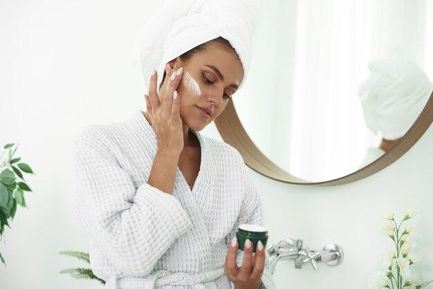Młoda kobieta z białym ręcznikiem na głowie