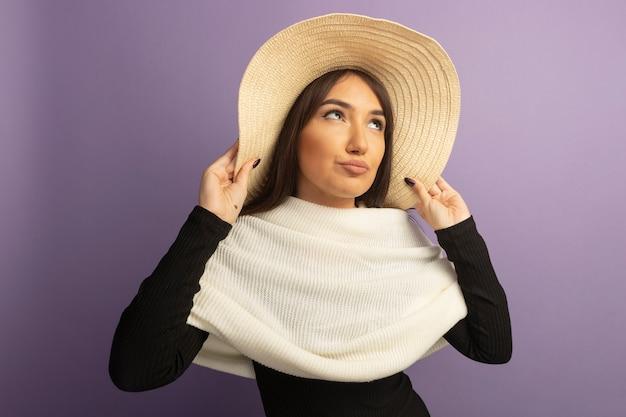 Młoda kobieta z białym szalikiem i letnim kapeluszem patrząc na bok z pewnym siebie wyrazem twarzy stojącej nad fioletową ścianą