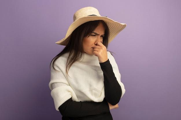 Młoda kobieta z białym szalikiem i letnim kapeluszem patrząc na bok zdezorientowany